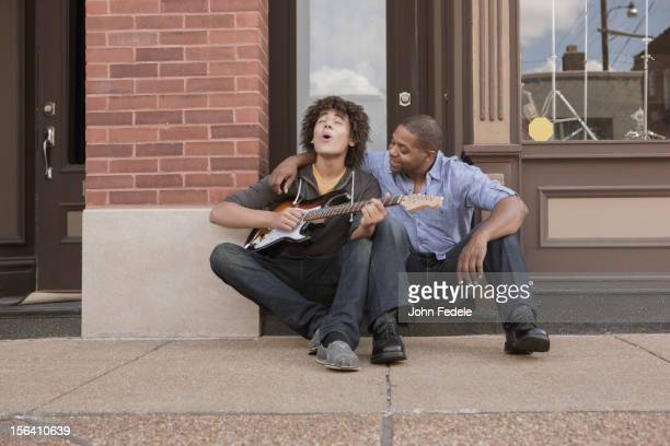 Father watching son playing electric guitar