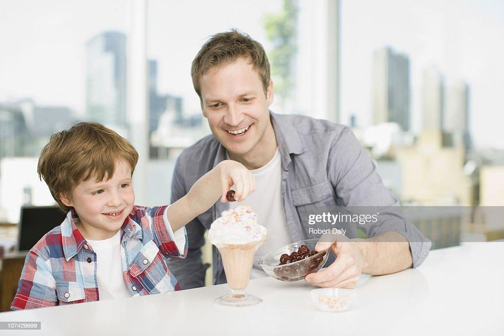 Father watching son put cherry on ice cream sundae : Stock Photo
