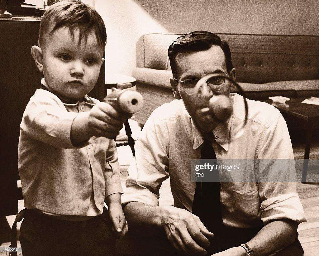 Father watching son (2-4) shoot toy gun (B&W sepia tone) : Stock Photo