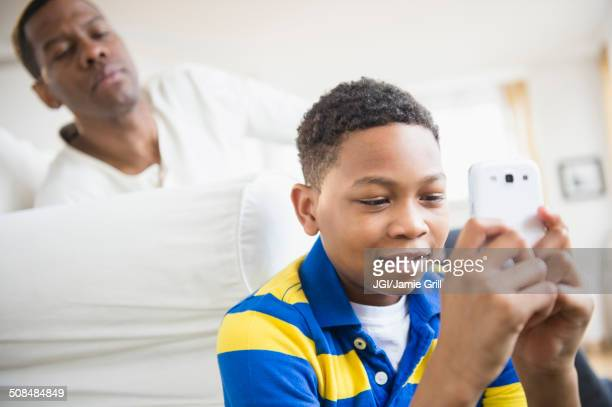 Father watching son use cell phone