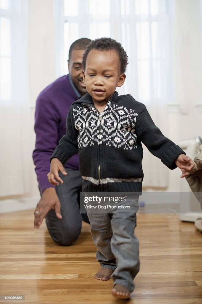 Father watching toddler walk : Stock Photo