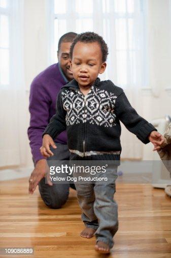 Father watching toddler walk : Stock Photo