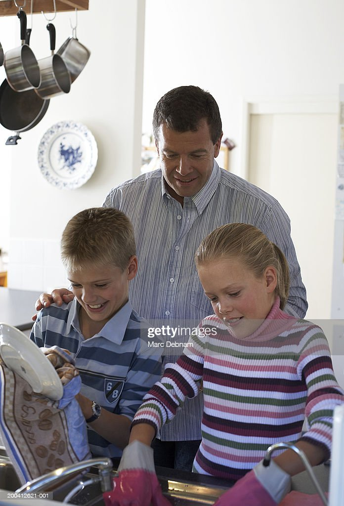 Father watching twins (10-12) washing and wiping up at kitchen sink : Stock Photo