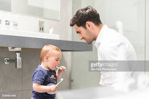 Father watching young brush teeth