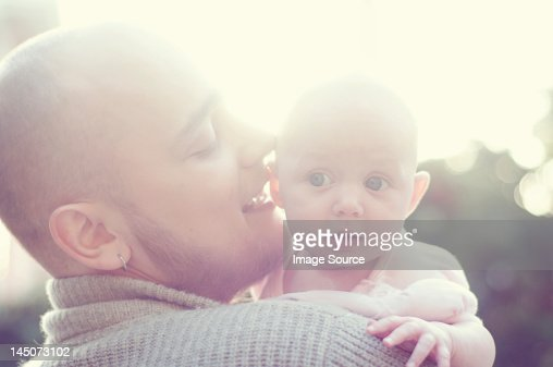 Father whispering to baby : Stock Photo