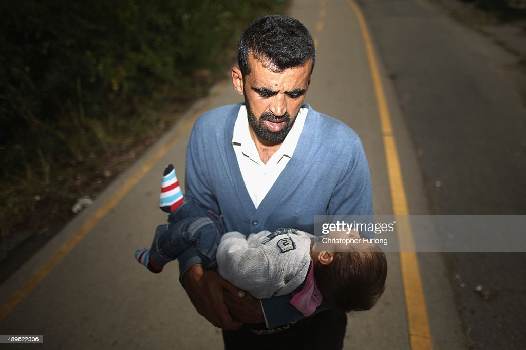 A father who arrived by train at Hegyeshalom on the Hungarian and Austrian border, carries his dehydrated son the four kilometres ito the Austrian border. The young boy was treated by volunteers of the Hungarian Red Cross and they continued their journey into Austria on September 23, 2015 in Hegyeshalom, Hungary. Thousands of migrants have arrived in Austria with more en-route from Hungary, Croatia and Slovenia. EU leaders are attending an extraordinary summit on today to try and solve the crisis.
