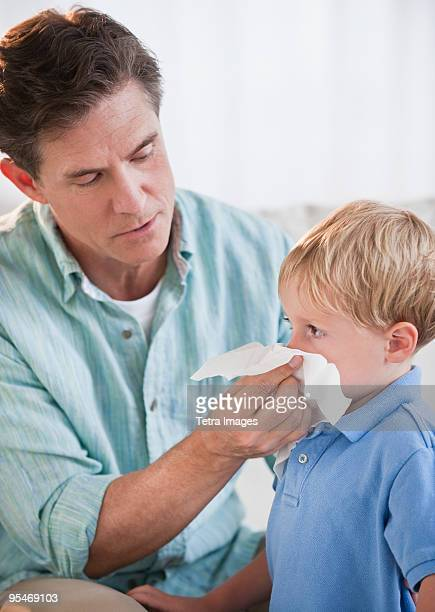 Father wiping child's nose