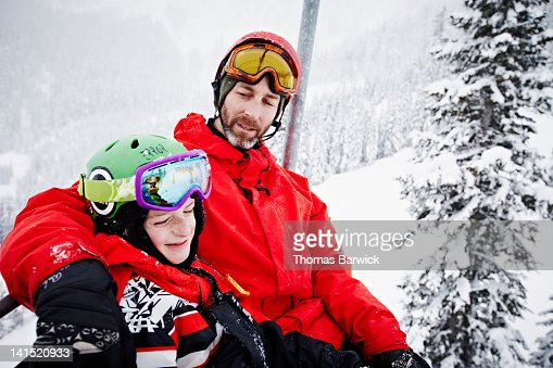 Father with arm around son riding chair lift