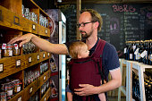 Father with baby daughter looking at jars in shop