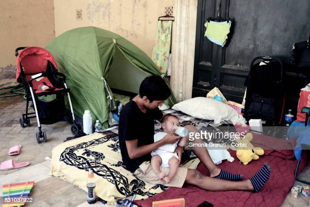 Father with baby in the Colonnade of the Basilica where lives with other families since August 11 after leaving the occupied palace in Quintavalle...