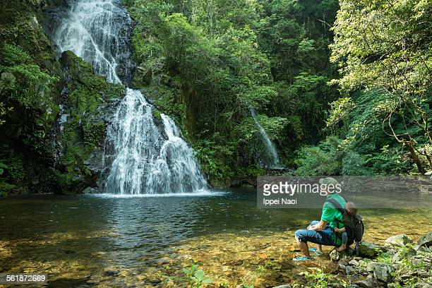 Father with baby relaxing by waterfall in forest