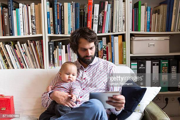 Father with baby son using tablet computer