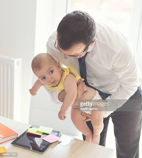 Vater mit Baby In das Büro zu Hause arbeiten