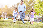 Father With Children Playing Soccer In Park Together Smiling