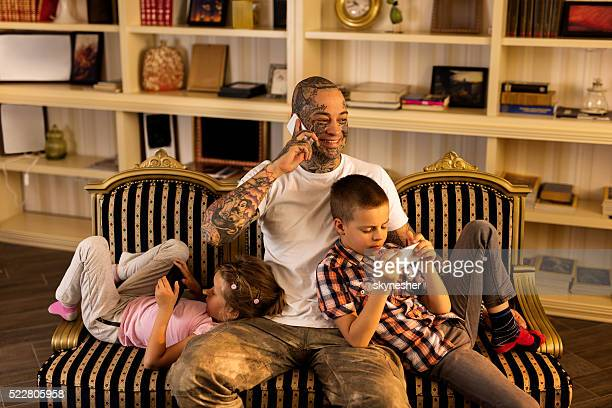 Father with children using wireless technology at home.