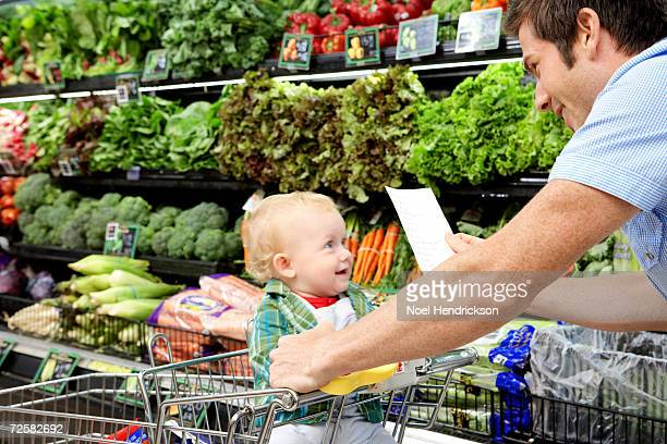 Father with daughter (9-12 months) and shopping list in supermarket