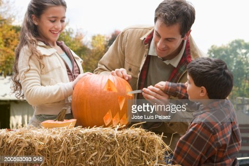 Father with daughter (8-9) and son (4-5) carving a pumpkin in garden : Stock Photo
