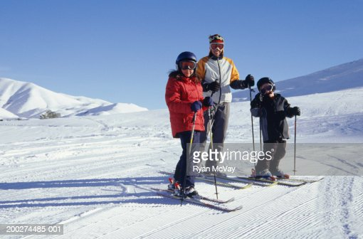 Father with daughter (8-9) and son (6-7) on ski slope, portrait : Stock Photo