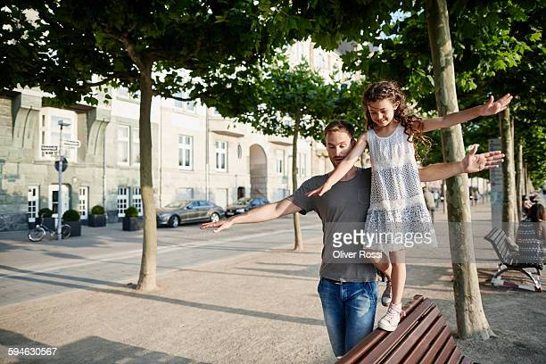 Father with daughter balancing on a bench