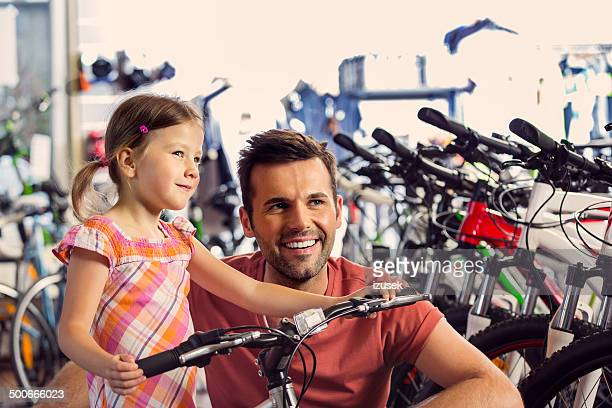 Father with daughter in bike store