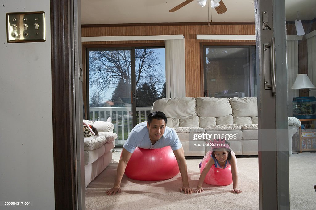 Father with daughter (4-5) lying on front on exercise ball : Stock Photo