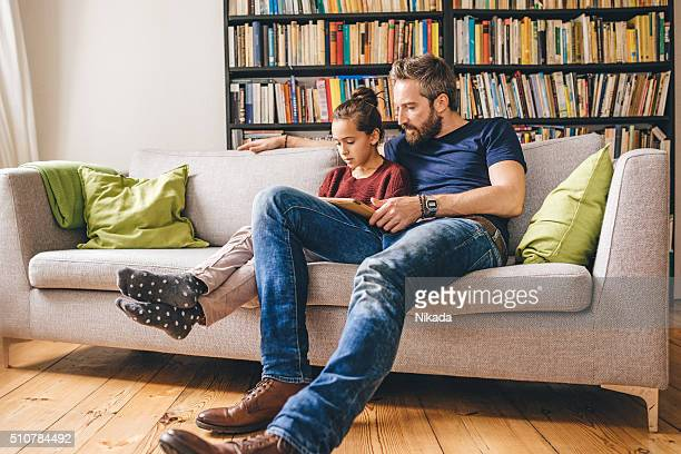 father with daughter on sofa using digital tablet