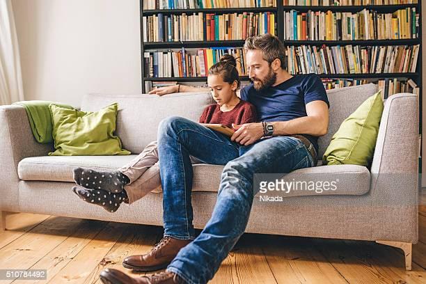 Père et fille sur le canapé à l'aide de tablette numérique