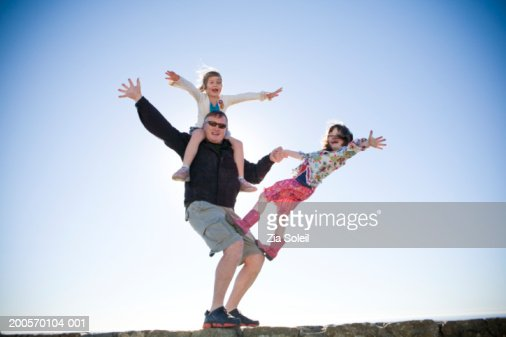 Father with daughter (6-7) playing circus acrobats on wall, low angle : Stock Photo