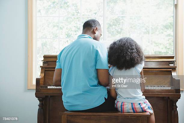 Father with daughter (6-7) playing piano, rear view