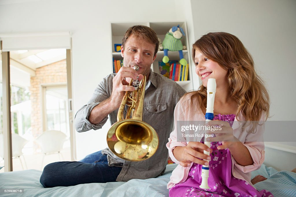 Father with daughter (8-9) playing trumpet and flute : Foto de stock