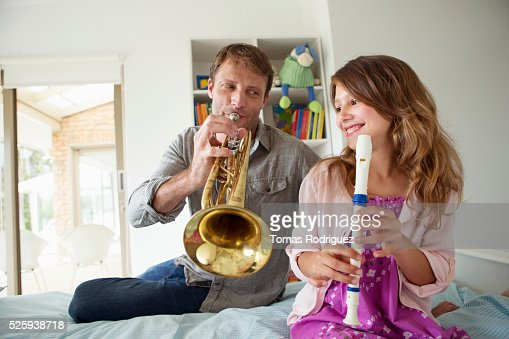 Father with daughter (8-9) playing trumpet and flute : Stock Photo