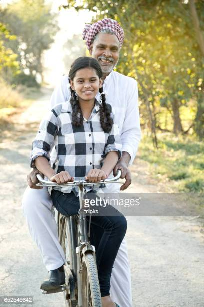 Father with daughter riding on bicycle