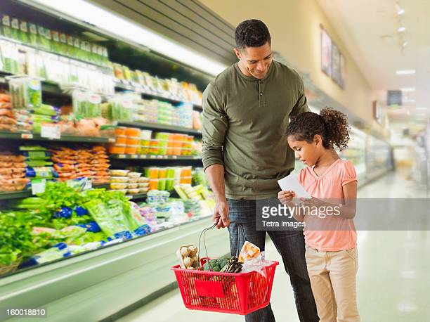 Father with daughter (6-7) shopping in supermarket