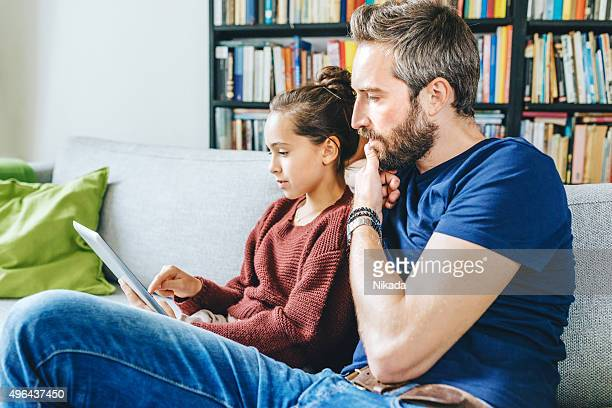father with daughter using digital tablet