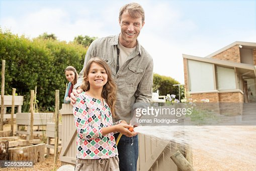 Father with daughter (8-9) watering vegetable garden : Foto stock