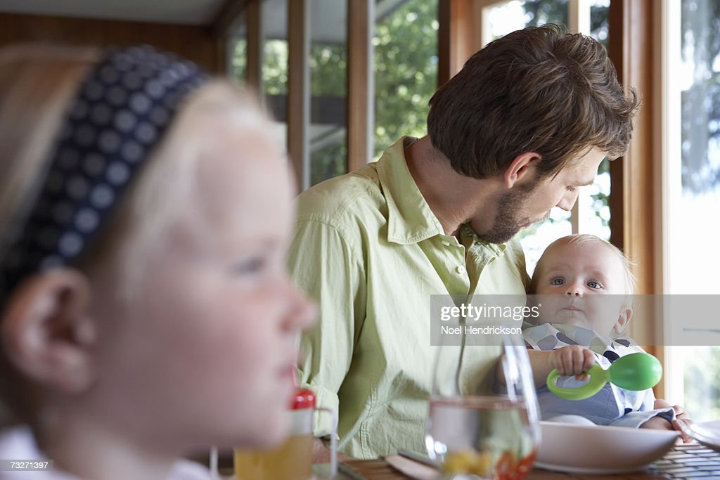 Father with daughters (5-7) and (9-12 months) eating meal at table : Stock Photo