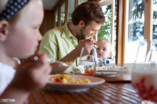 Père avec leurs filles (5-7) et de (9-12 mois) manger repas, se concentrer