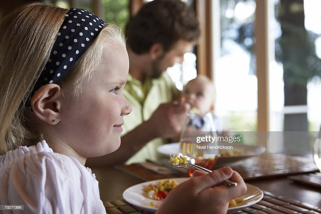 Father with daughters (5-7) and (9-12 months) eating meal, focus on older girl : Stock Photo