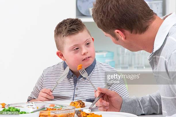 Vater und Sohn Essen Mahlzeit mit Behinderungen wie zu Hause fühlen.