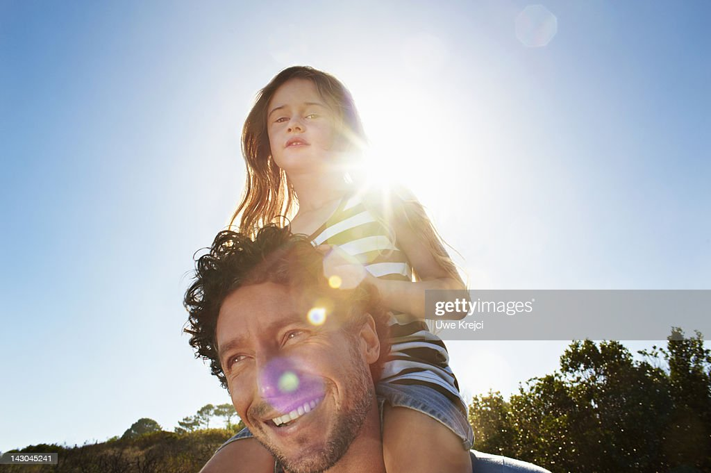 Father with girl (4 -6) on shoulders, outdoors : Stock Photo