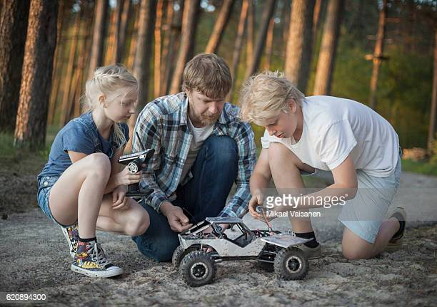 Father with his 2 children playing with remote controlled car