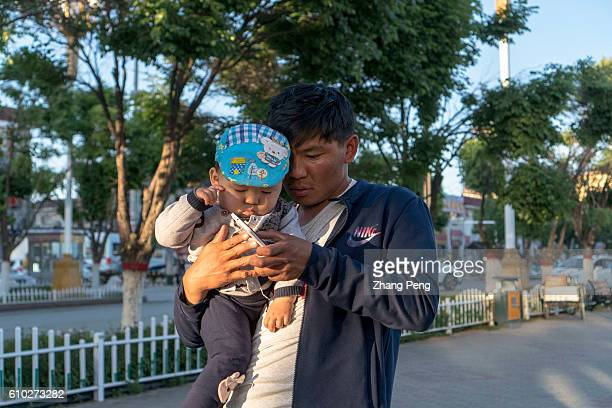 A father with his baby boy plays mobile phone on the street China has allowed all couples to have two children in 2016 but young Chinese couples...