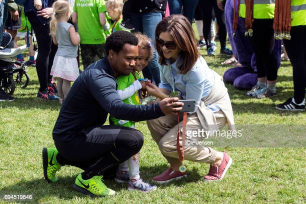 A father with his child takes a selfie with medal presenter Crown Princess Mary of Denmark at the 'Children's Relay Run' in Faelledparken on June 10...