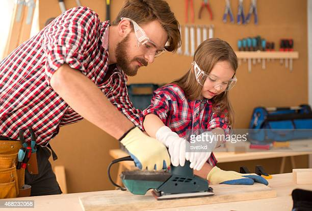 Father with his cute little daughter in woodshop.