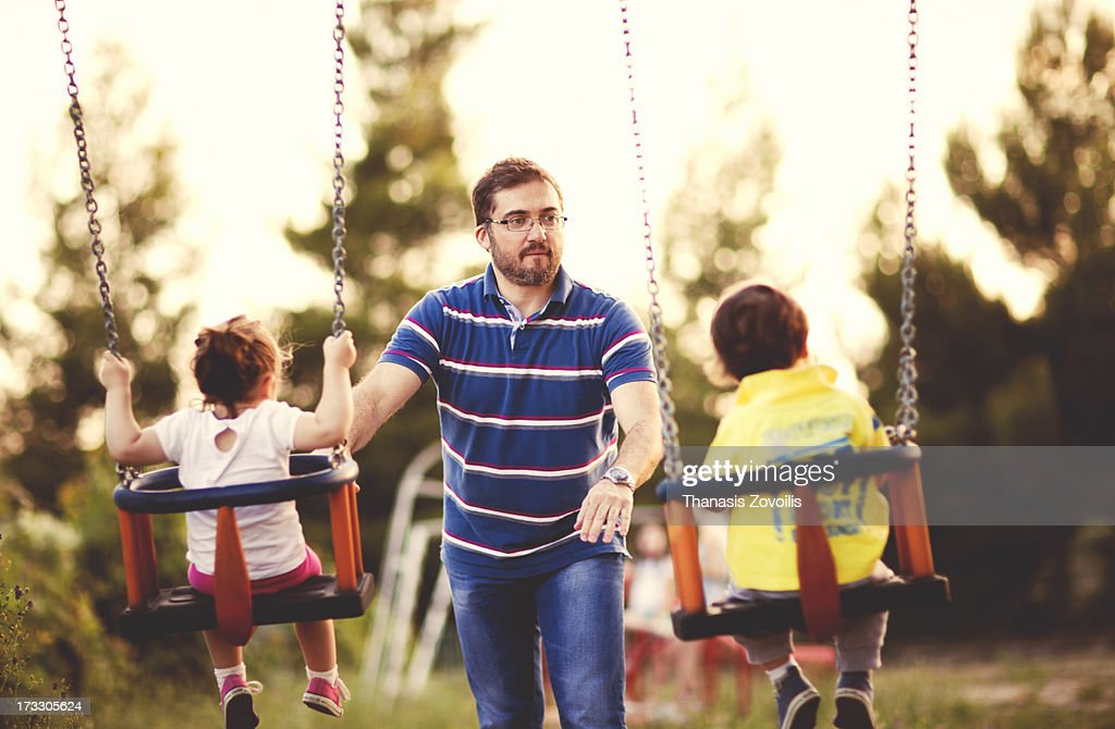 Father with his kids in a playground : Stock Photo