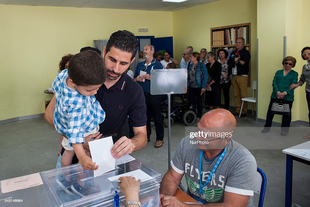 A father with his son places his vote at a polling station during elections Santander June 26 in Spain . Spanish voters head back to the polls after the last election in December failed to produce a government. Latest opinion polls suggest the Unidos Podemos left-wing alliance could make enough gains to come in second behind the ruling center right Popular Party.