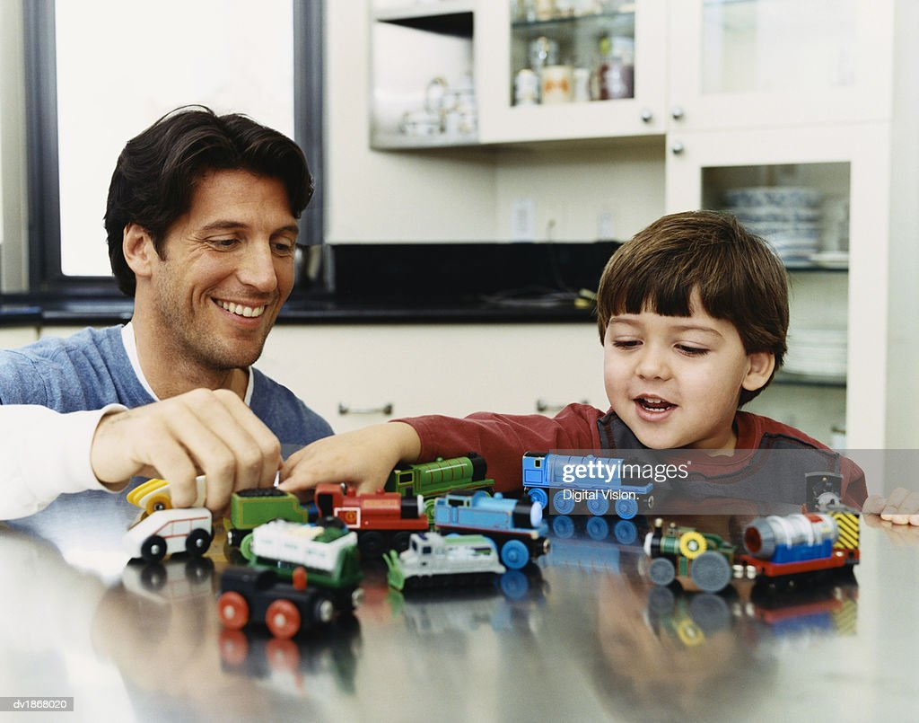 Father With His Son Playing With a Toy Train Set on a Metallic Kitchen Counter