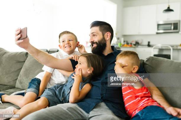 Father with his three children (2-3, 6-7) taking selfie with smart phone