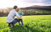 A father with his toddler son outside in green sunny spring nature. Rear view. Copy space.