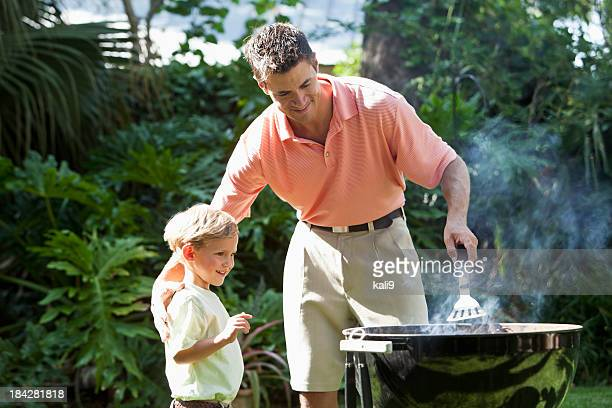 Father with little boy cooking on barbecue grill